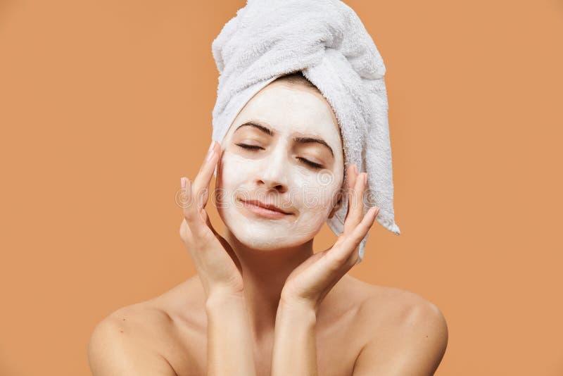 Ung kvinna med stängda ögon och bärande mouisturizing ansikts- maskering för fridsamt ansiktsuttryck på hennes framsida Wellness  fotografering för bildbyråer