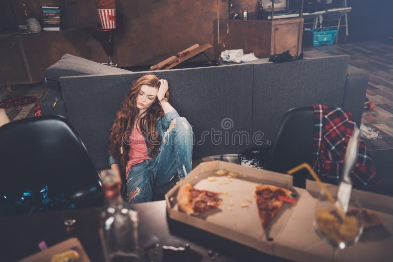 Ung kvinna med stängda ögon som sitter på golv i smutsigt rum efter parti royaltyfri foto