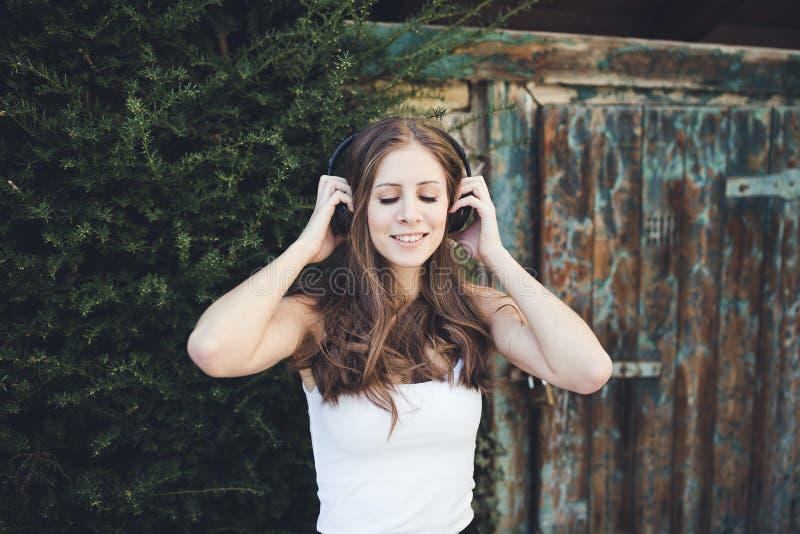 Ung kvinna med stängda ögon som utomhus lyssnar till musik via hörlurar royaltyfri foto