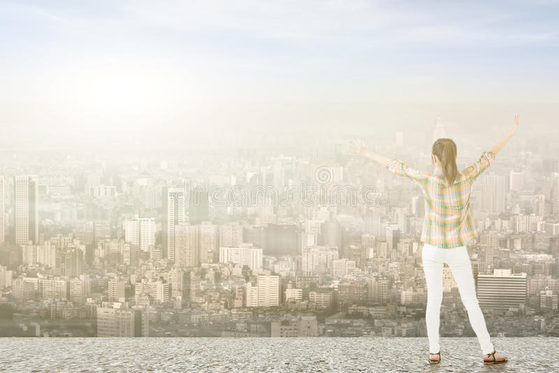 Ung kvinna med sträckta armar som ser staden arkivbilder