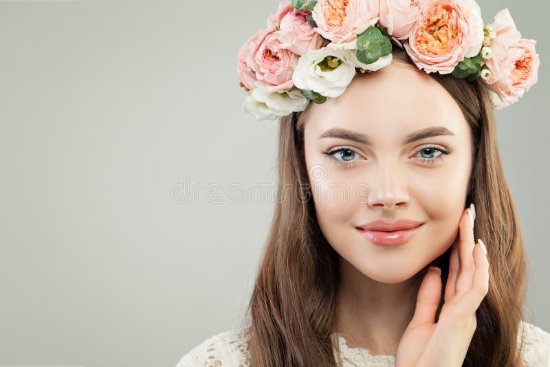 Ung kvinna med sund klar hud, brunt hår, naturlig makeup och blommakransen på hennes huvud, modeskönhetstående fotografering för bildbyråer
