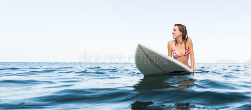 Ung kvinna med surfingbrädan royaltyfria foton