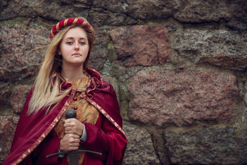 Ung kvinna med svärd i hand på stenväggbakgrund med kopieringsutrymme royaltyfri fotografi