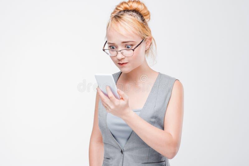 Ung kvinna med telefonen som är ilsken, irriteras och irriteras royaltyfria bilder