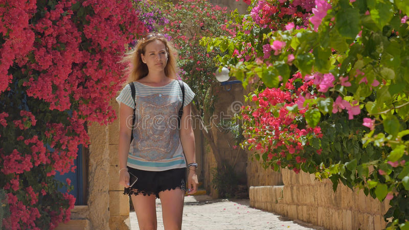 Ung kvinna med telefonen som promenerar den gamla gatan i tropisk stad arkivbild