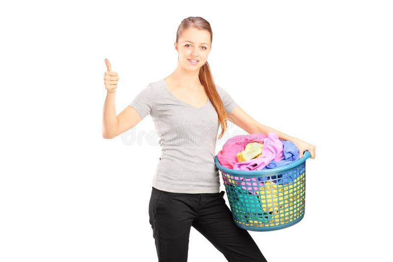 Ung kvinna med tvättkorgen som är full av kläder som ger upp tummen royaltyfria bilder