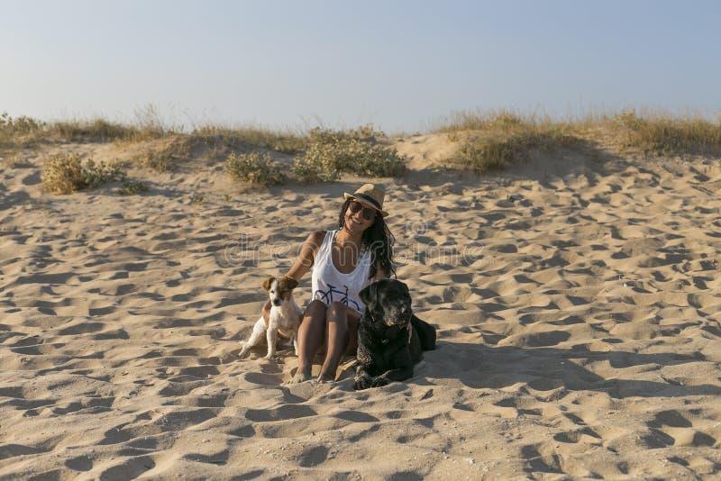 Ung kvinna med två hundkapplöpning på stranden unga vuxen m?nniska royaltyfri foto