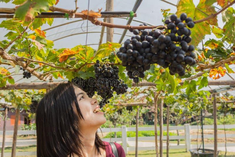 Ung kvinna med utomhus- druvor royaltyfria foton
