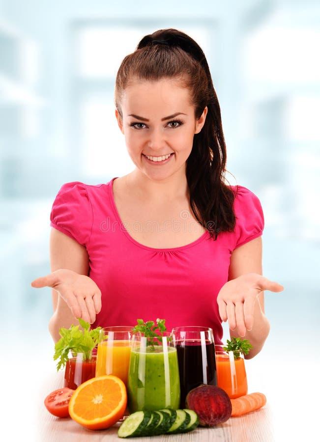 Ung kvinna med variation av grönsak- och fruktfruktsafter royaltyfria foton
