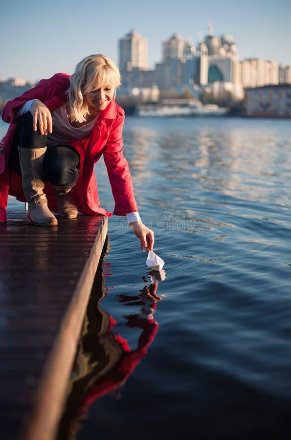 Ung kvinna mot floden som spelar med det pappers- skeppet fotografering för bildbyråer