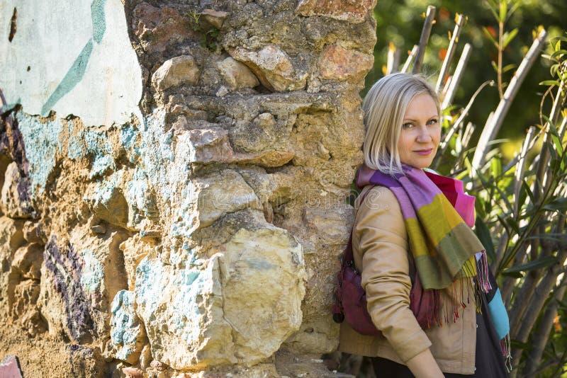Ung kvinna nära gamla stenväggar i parkera arkivbilder
