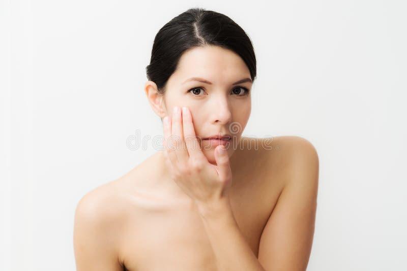 Ung kvinna observera ansiktsbehandlingskrynklor arkivfoton