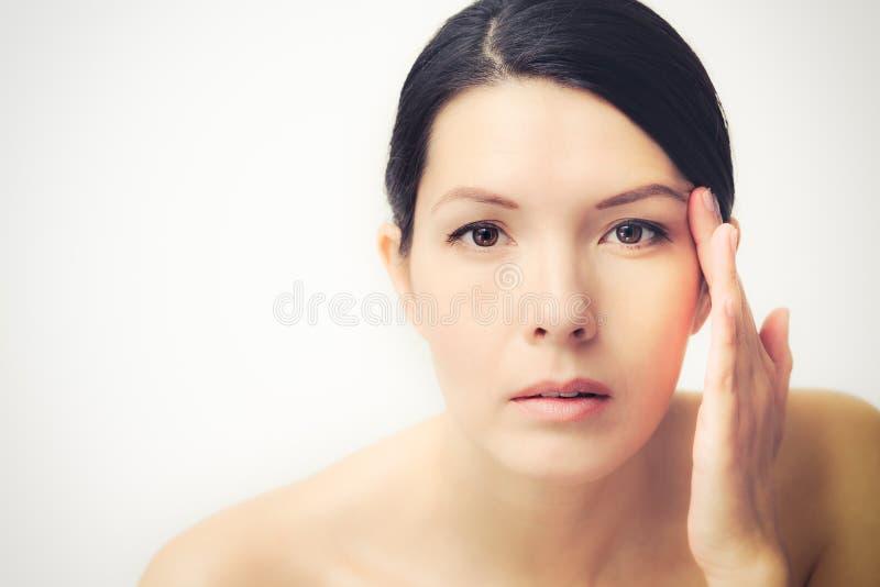 Ung kvinna observera ansiktsbehandlingskrynklor royaltyfria foton