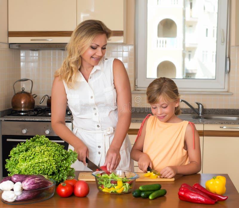 Ung kvinna och flicka som gör sallad för ny grönsak Sunt inhemskt matbegrepp Moder och dotter som tillsammans lagar mat, hjälpbar royaltyfri foto