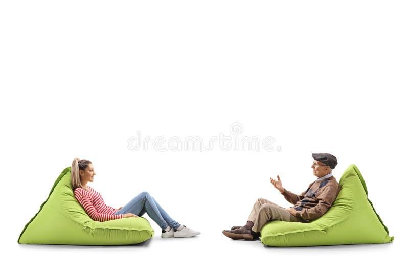 Ung kvinna och hög en man som sitter på bönapåsar och har en konversation royaltyfria foton