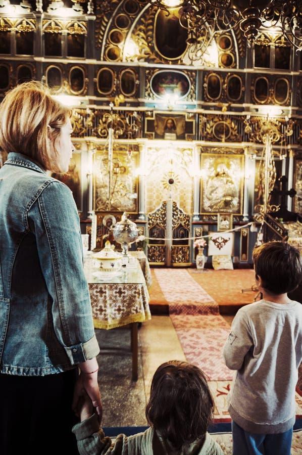 Ung kvinna och hennes barn i en kyrka arkivfoton