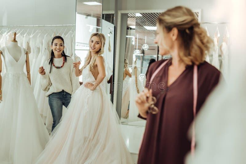 Ung kvinna och hennes brudtärna i en gifta sig salong arkivfoto