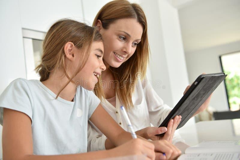 Ung kvinna och hennes dotter som använder minnestavlan arkivfoto