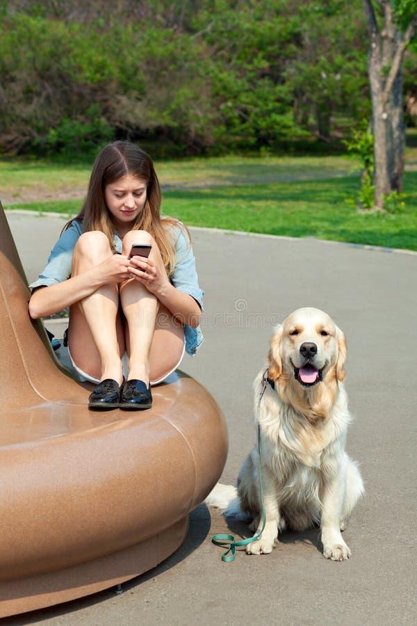 Ung kvinna och hennes hundgolden retriever i parkera på en sommardag arkivfoton