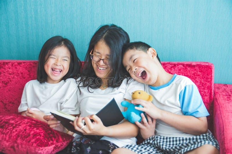 Ung kvinna och hennes läseböcker för små barn på soffan på hom arkivbild