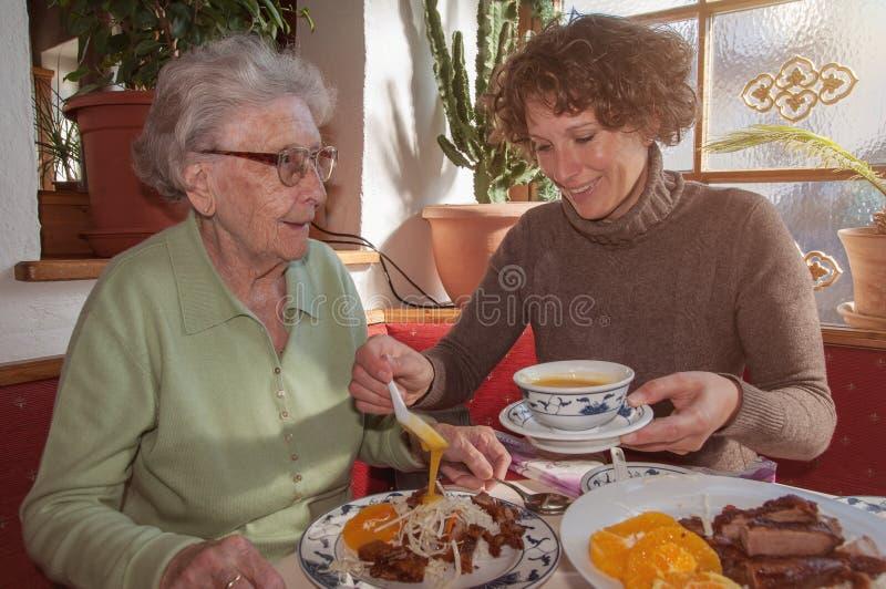 Ung kvinna och hennes lycklig farmor som har lunch på restaurangen arkivfoton