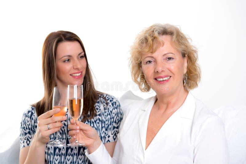 Ung kvinna och hennes moder som dricker champagne arkivfoto