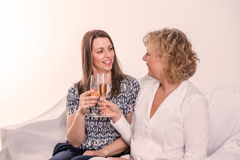 Ung kvinna och hennes moder som dricker champagne royaltyfri bild