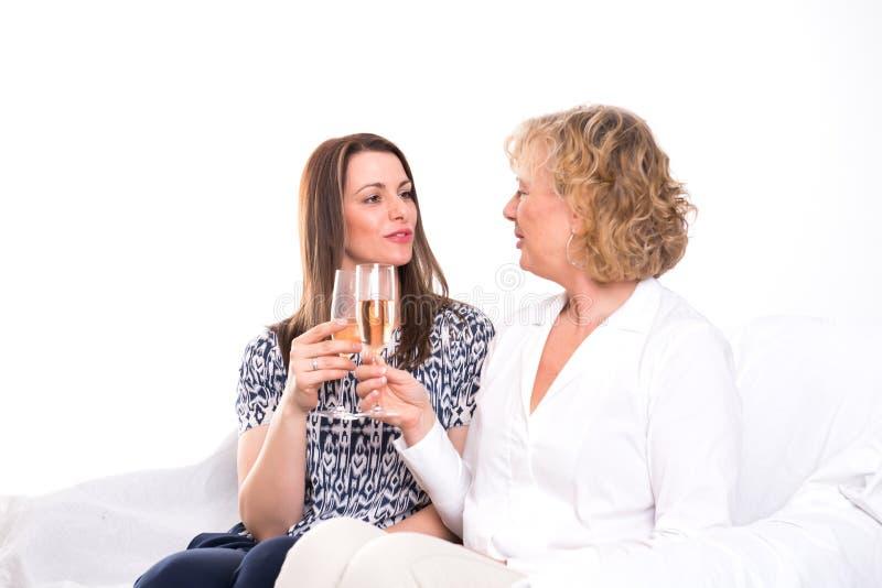 Ung kvinna och hennes moder som dricker champagne royaltyfria foton