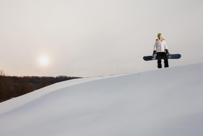 Ung kvinna och hennes snowboard på dentäckte bergssidan royaltyfri bild