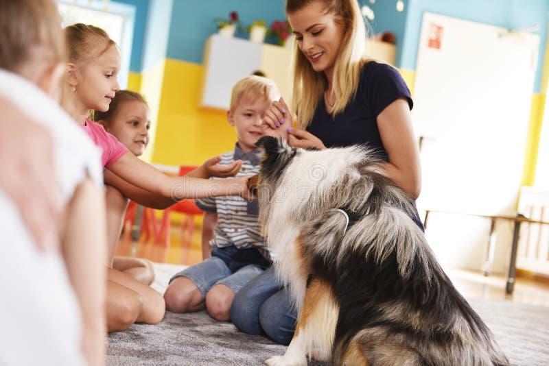 Ung kvinna och hennes terapihundarbete med barn royaltyfri fotografi