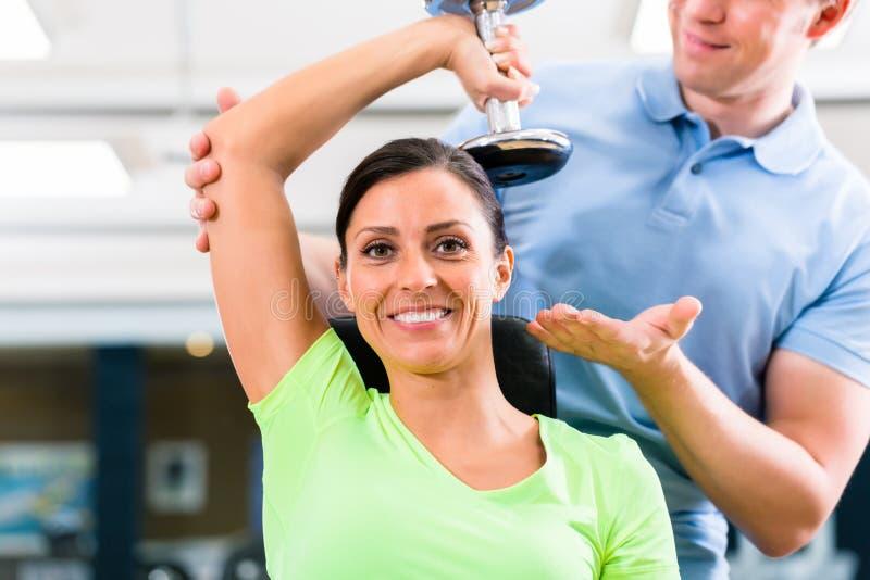 Ung kvinna och instruktör på övningen i idrottshall arkivbilder