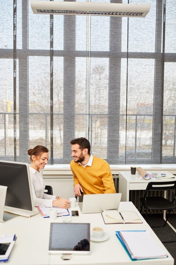 Ung kvinna och konsulterande flörta på arbete arkivfoto