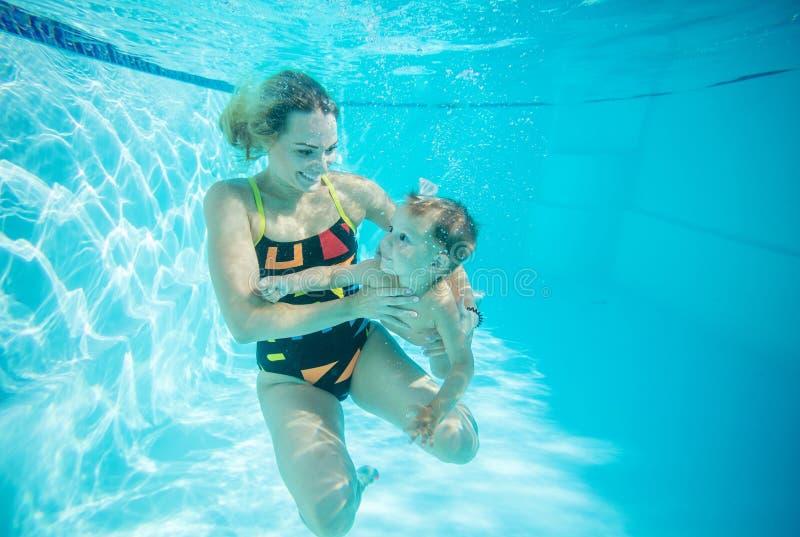 Ung kvinna och litet simma för son som är undervattens- royaltyfria bilder