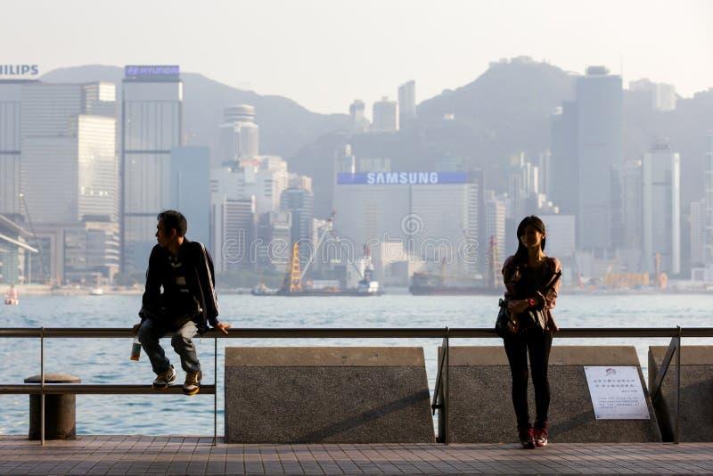 Ung kvinna och man på Tsimen Sha Tsui Promenade arkivfoto