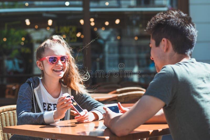 Ung kvinna och man som sitter i trottoarkafét som talar och använder mobiltelefoner royaltyfria bilder