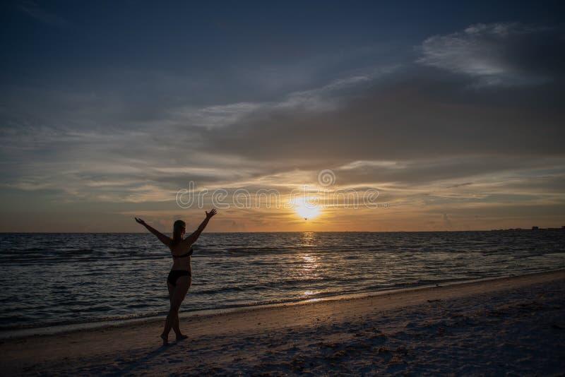 Ung kvinna och solnedgång på stranden royaltyfria foton