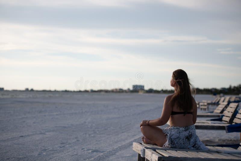 Ung kvinna och solnedgång på stranden royaltyfri fotografi