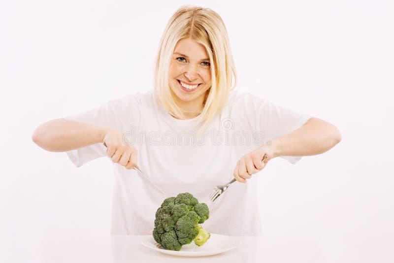 Ung kvinna omkring som äter broccoli från en platta fotografering för bildbyråer