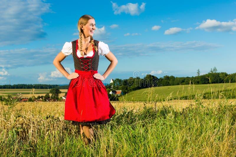 Ung kvinna på äng som ha på sig dirndlen arkivfoton