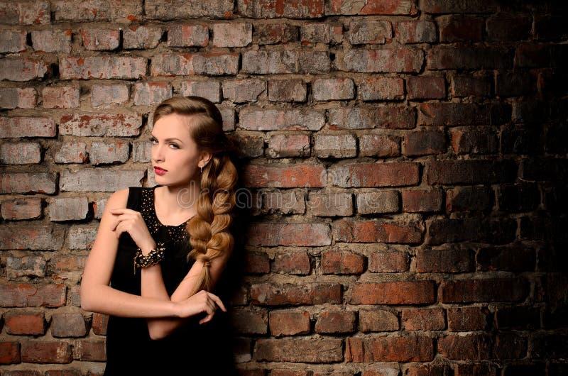 Ung kvinna på bakgrund för tegelstenvägg royaltyfria foton