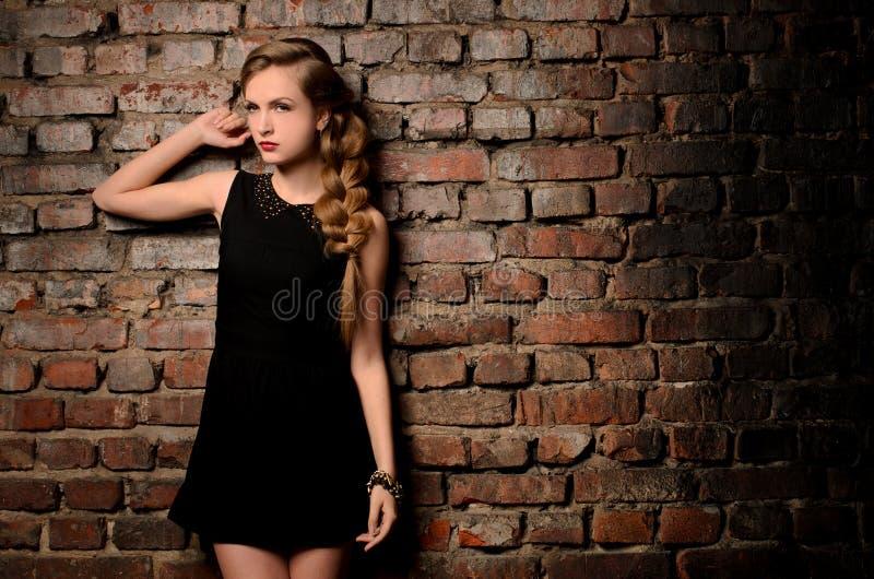 Ung kvinna på bakgrund för tegelstenvägg royaltyfria bilder