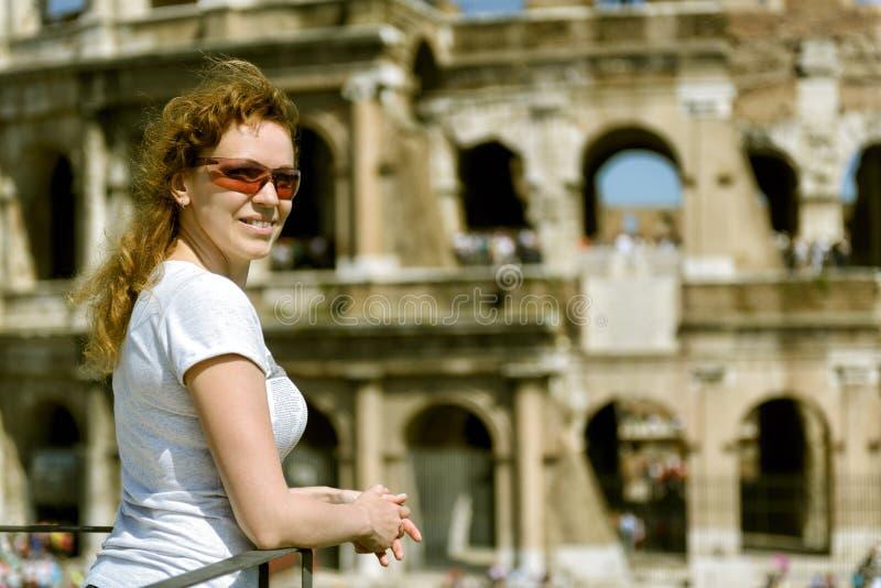 Ung kvinna på bakgrunden av Colosseumen i Rome arkivbilder