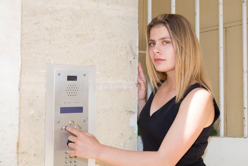 Ung kvinna på byggnadshögtalaranläggningtelefonen i gata arkivbild