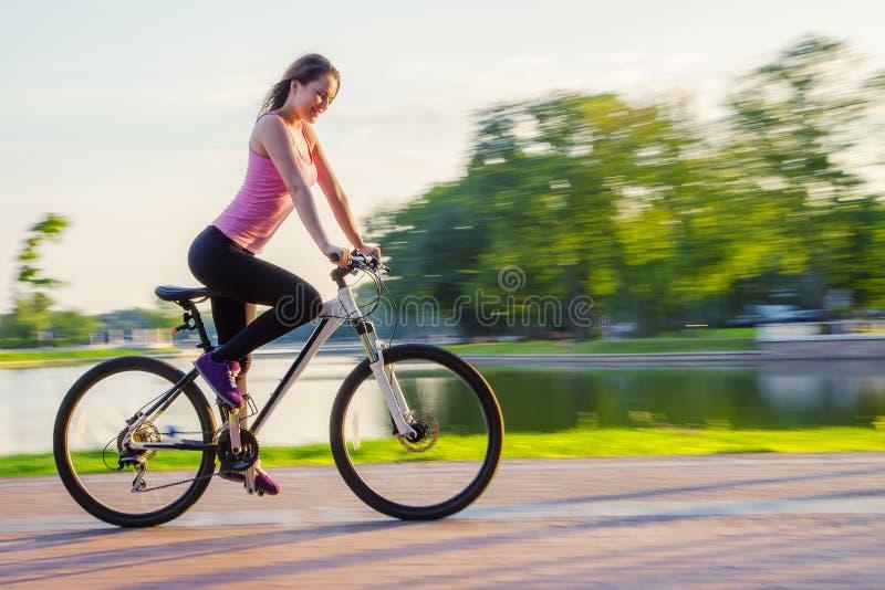 Ung kvinna på cykeln arkivbild