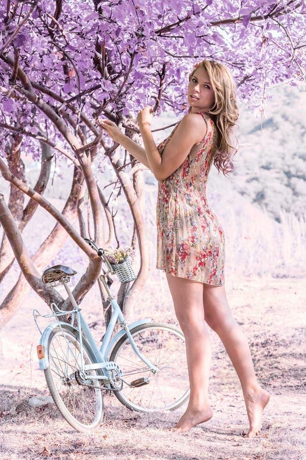 Ung kvinna på cykeln i fantasirosa färgskog arkivbilder