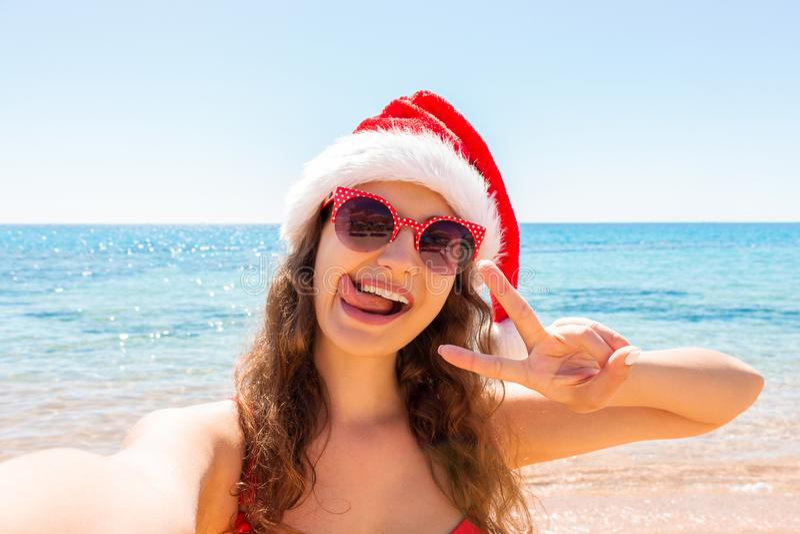 Ung kvinna in på den tropiska stranden Tar den iklädda modebaddräkten för den unga sexiga kvinnan och den santa hatten som använd royaltyfria foton