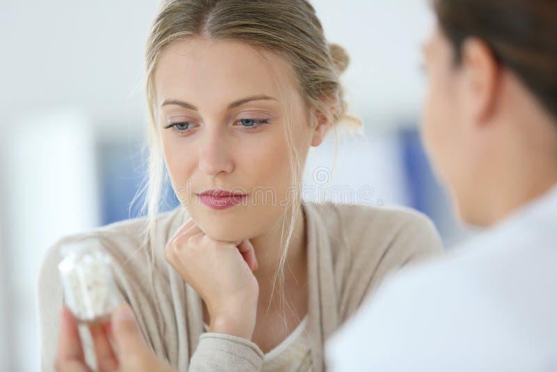 Ung kvinna på doktors fående preventivpillerar royaltyfri foto