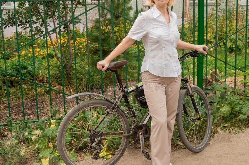 Ung kvinna på en cykel som står vägen i parkera royaltyfria bilder