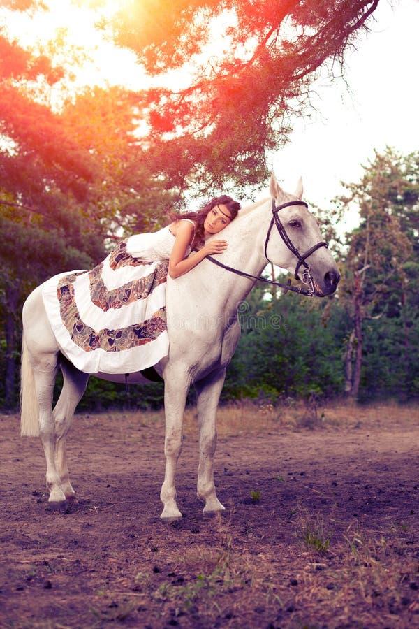 Ung kvinna på en häst Hästryggryttare, kvinnaridninghäst royaltyfri fotografi