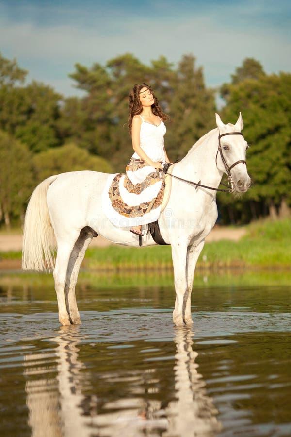 Ung kvinna på en häst Hästryggryttare, kvinnaridninghäst på b fotografering för bildbyråer